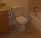 Toliet Next to Cabinet and Tub